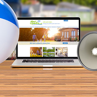 A beach ball and loudhaler sit next to a laptop with the Your Parks website